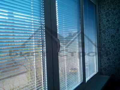 Голубые горизонтальные жалюзи на окне